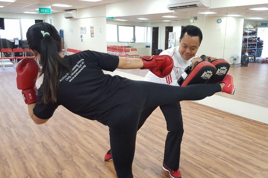 Kickboxing Federation of Singapore president Jason Lim (in white, holding pads) was named on the development committee of the World Association of Kickboxing Associations.