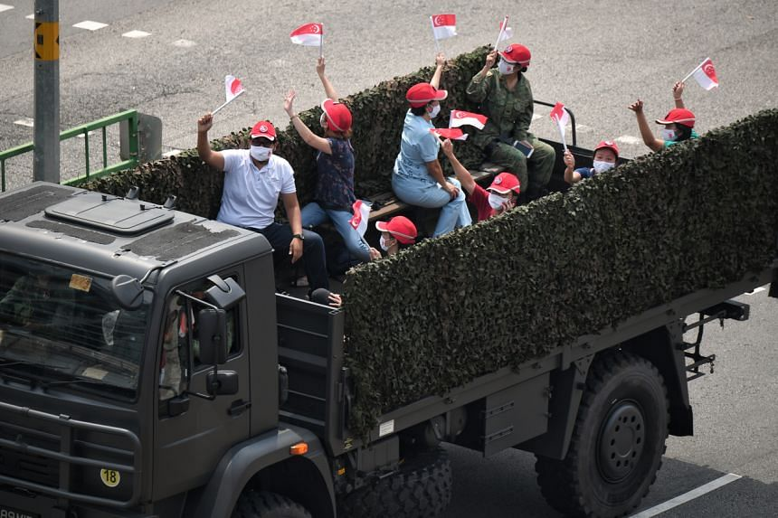 A truck with front-liners on board moving along Toa Payoh Lorong 1 as part of a mobile column contingent on National Day earlier in 2020.