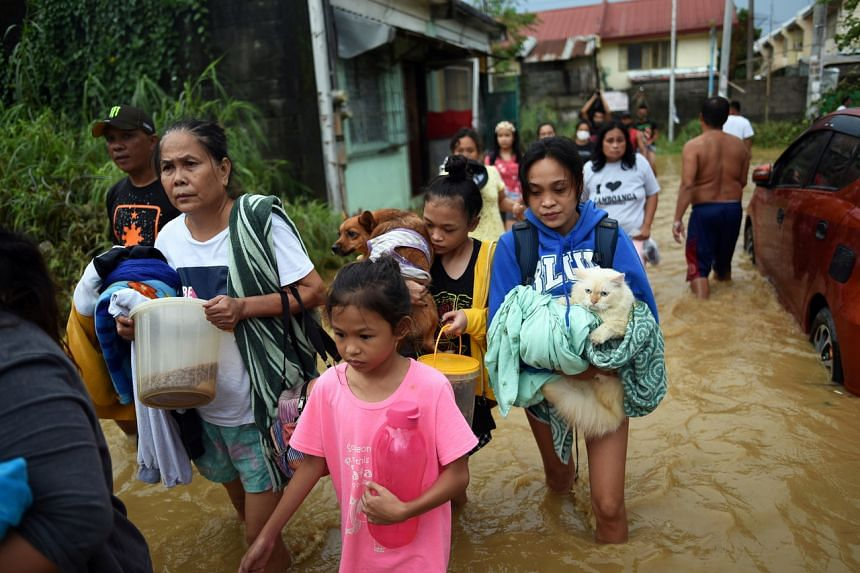 Residents wade through a flooded street following Typhoon Vamco, in Rizal Province, Philippines, on Nov 12, 2020.