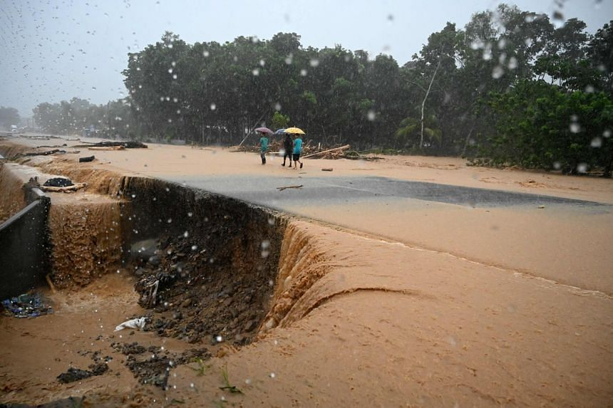 Men walk along a flooded road after the River Chirichil overflowed following heavy rains caused during the passage of Hurricane Eta in Toyos, Honduras, on Nov 4, 2020.
