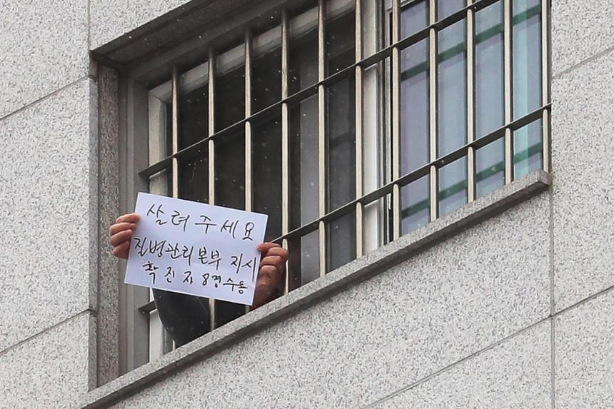 An inmate infected with Covid-19 holds up a message reading 'save me' through a window at Dongbu Detention Center in Seoul, South Korea, Dec 29, 2020.