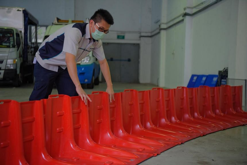 PUB assistant engineer Vincent Tay installs a portable flood barrier during a demonstration.