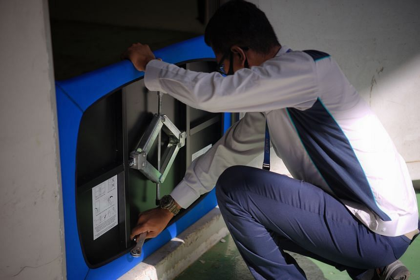 PUB assistant engineer Mohammad Fahmi Vasmin tightens the bottom bolts of a floodgate during a demonstration.
