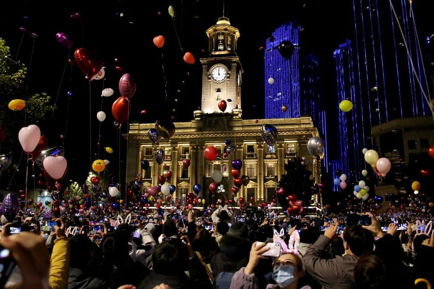People hold balloons as they gather to celebrate the arrival of the new year, in Wuhan, China.