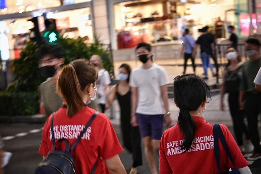 Safe distancing ambassadors in Singapore remind people to adhere to measures put in place to stem the spread of the coronavirus. These measures include the wearing of masks, restrictions on group sizes, and keeping a 1m distance between groups. ST PH