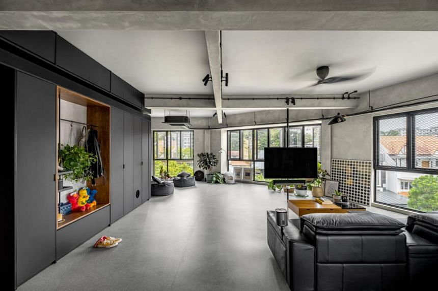 The unit is a sun-drenched open-plan apartment with a dark and sleek material palette.
