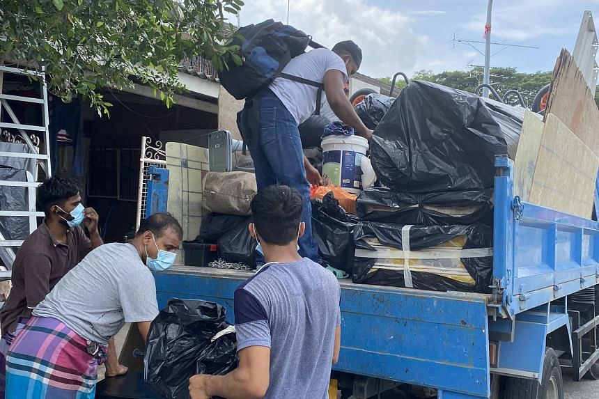 Migrant workers loading up their belongings on to a lorry at Geylang Lorong 3 on Dec 31, 2020.