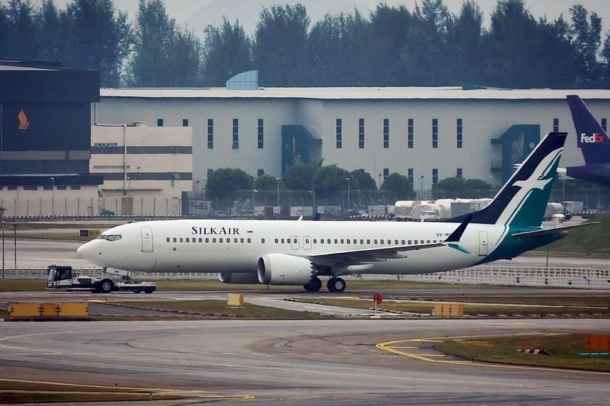 A SilkAir Boeing 737 Max 8 plane (foreground) sits on the tarmac at Changi Airport in March 2019.