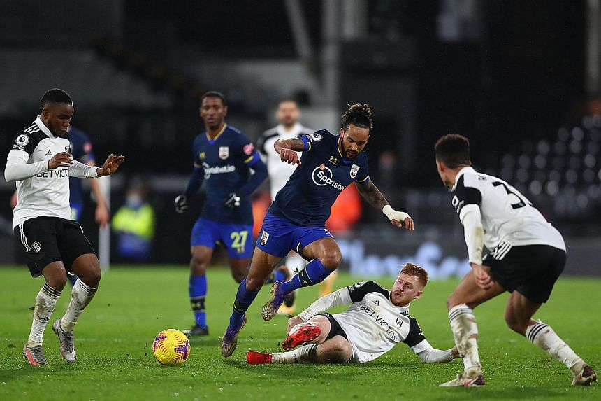 Southampton's Theo Walcott fights for the ball with Fulham's Harrison Reed in London on Dec 26, 2020.