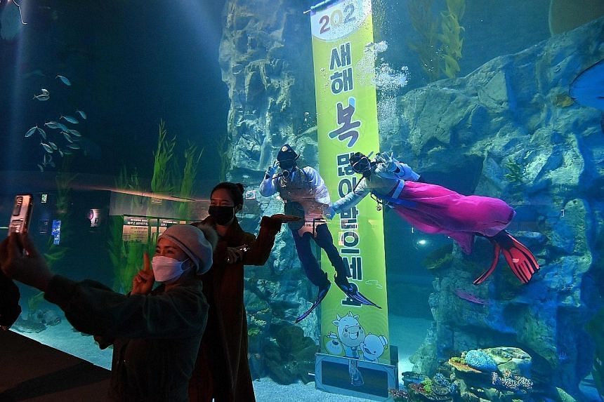 Visitors posing for photos with divers wearing South Korea's traditional hanbok costume at Lotte World Aquarium in Seoul yesterday. Despite the festive fun, the aquarium was quiet as many people refrained from going out amid the third and largest wav