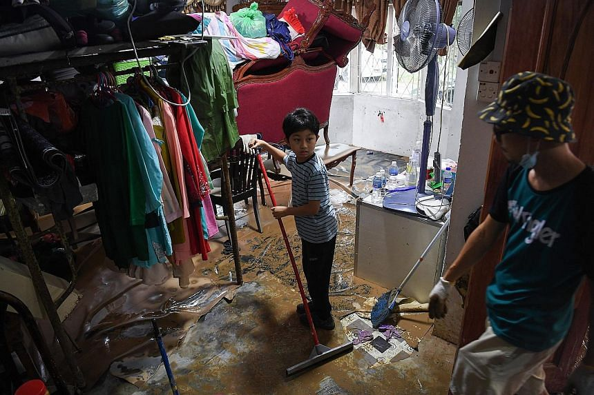 Family members cleaning their flood-hit home yesterday in Kampung Sepakat Baru in Skudai, Johor. Three river monitoring stations in the state recorded dangerous levels yesterday.