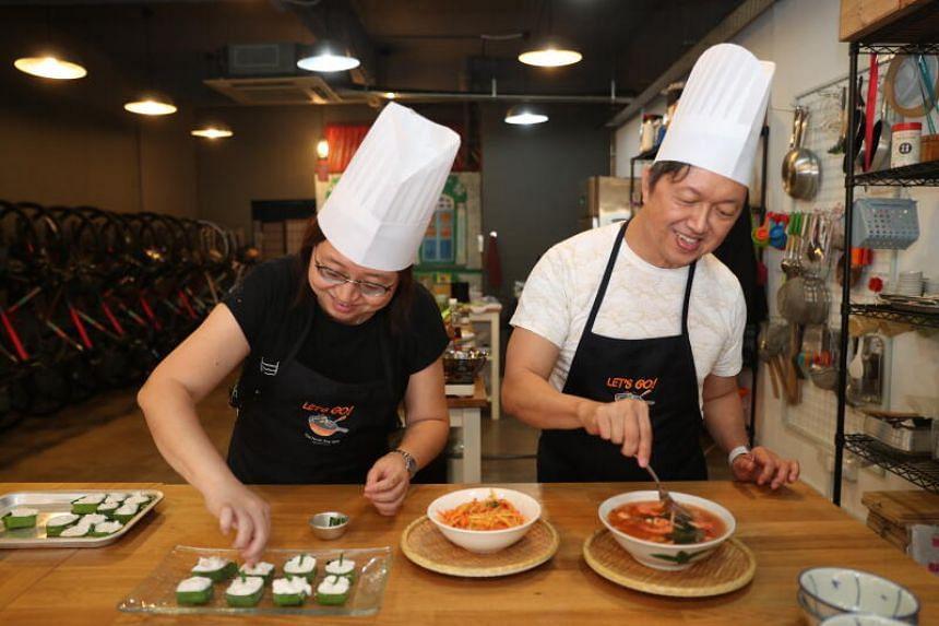 ST Food Critic Wong Ah Yoke (right) and Senior Culture Correspondent Ong Sor Fern adding finishing touches to Tom Yum Goong, Papaya salad and Thai Tako.