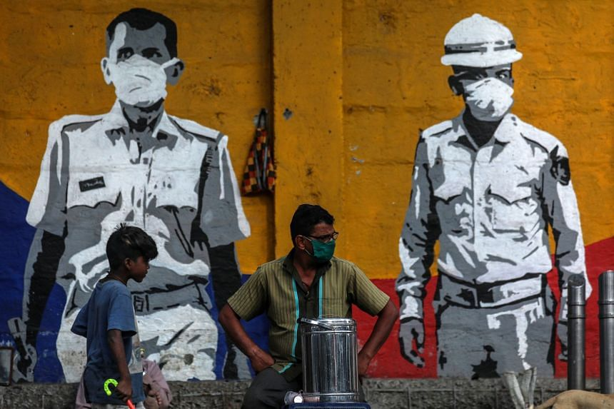 People sit in front of a wall honouring frontline workers in the fight against coronavirus, in Mumbai, India.
