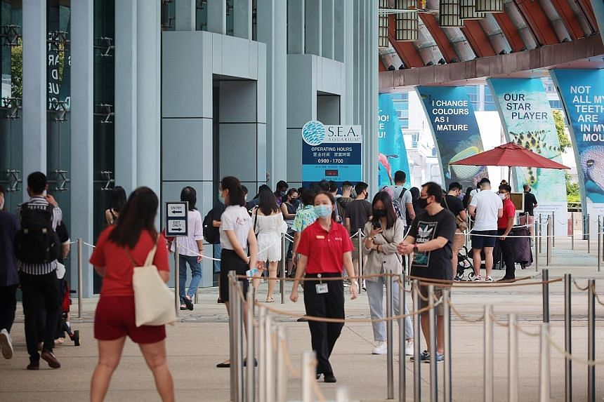 Visitors queueing outside S.E.A. Aquarium on Sentosa last month. Various places have introduced time slots to prevent overcrowding, and during the school holidays, many reportedly could not use their tickets for fully booked attractions. The Singapor