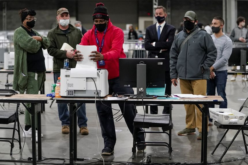 An election official puts absentee ballots in a scanner at the Georgia World Congress Center in Atlanta on Jan 5, 2021.