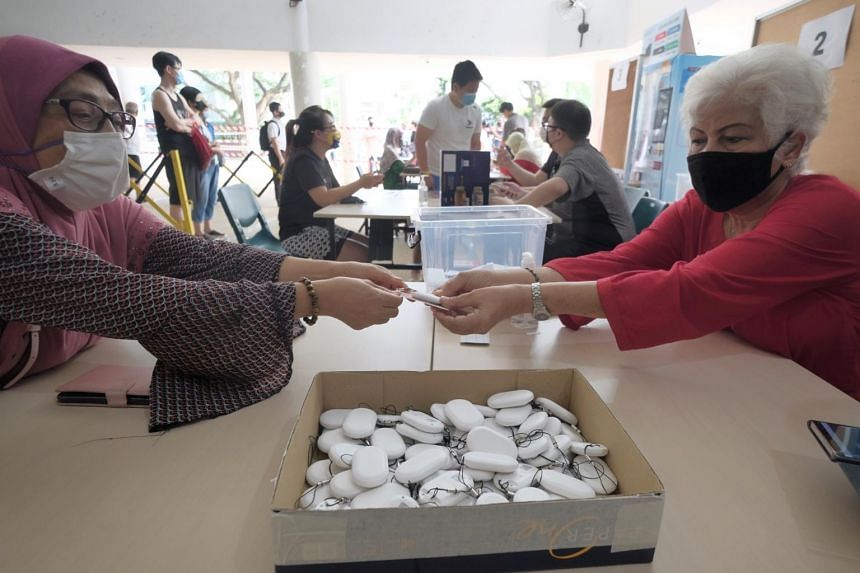 Residents collect their TraceTogether tokens at Kampong Kembangan Community Club.