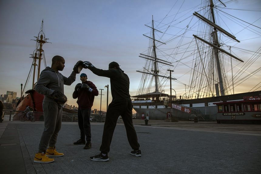 (From left) Boxing instructor Ralph Gilmore trains Dwayne Thomas and Greg Elysée near Pier 17 at the South Street Seaport.