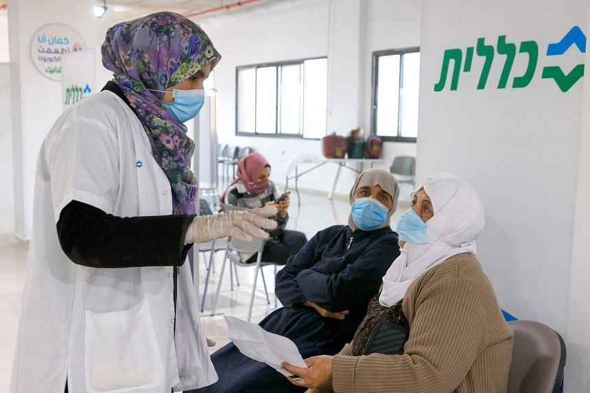 A healthcare worker speaks to an Arab Israeli woman before giving her a Covid-19 vaccine, on Jan 4, 2021.