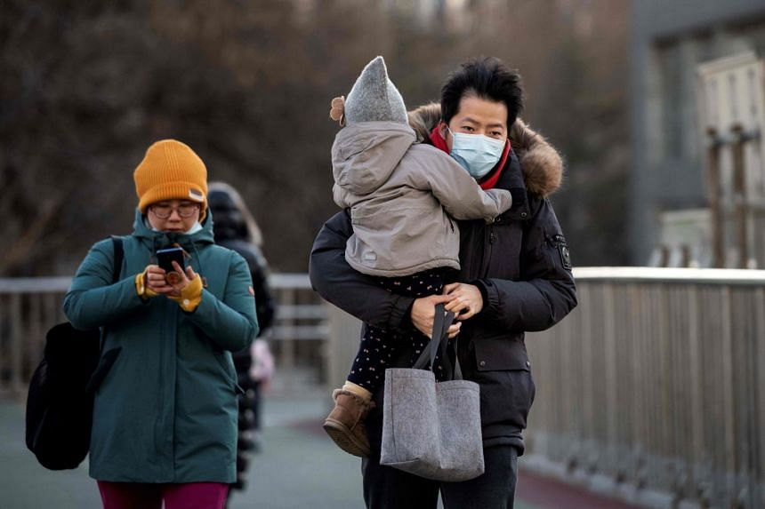 People wrapped up due to freezing weather walk on an overpass in Beijing on Jan 6, 2021.