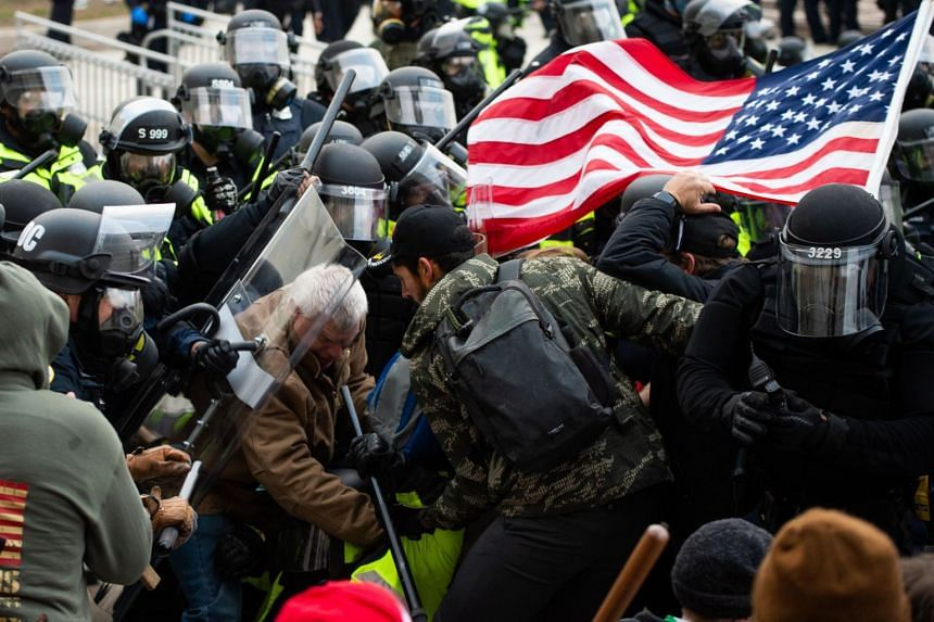 Supporters of US President Donald Trump clashing with riot police outside the Capitol building in Washington on Jan 6, 2021.