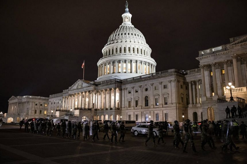 Police officers stand guard after a protest outside of the US Capitol in Washington on Jan 6, 2021.