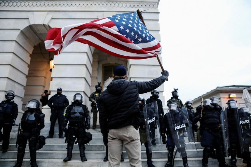 A supporter of US President Donald Trump confronting law enforcement officers in Washington, on Jan 6, 2021.