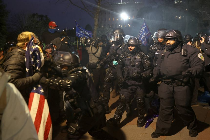 Police officers in riot gear confront protesters in Washington on Jan 06, 2021.