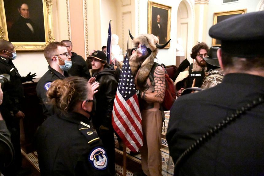 Police confronting supporters of US President Donald Trump as they demonstrate on the second floor of the US Capitol in Washington on Jan 6, 2021.