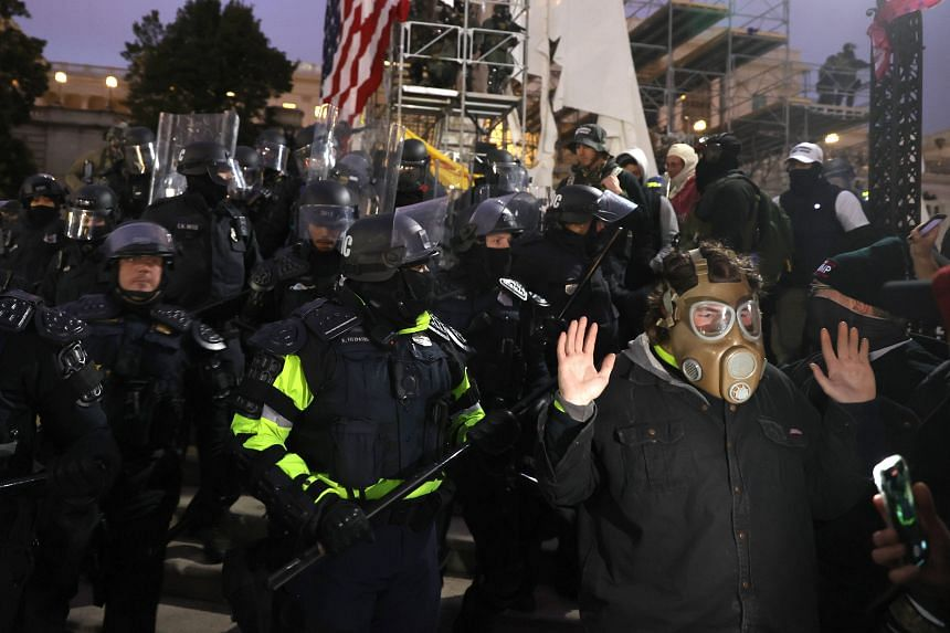 Police officers in riot gear moving protesters gathering in Washington on Jan 6, 2021.