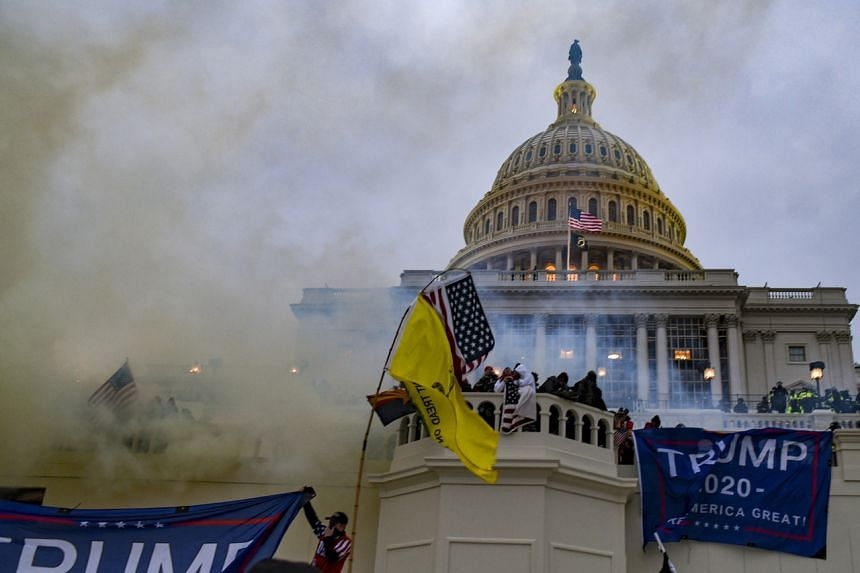 Trump supporters swarming the Capitol in Washington as the authorities deploy tear gas on Jan 6, 2021.