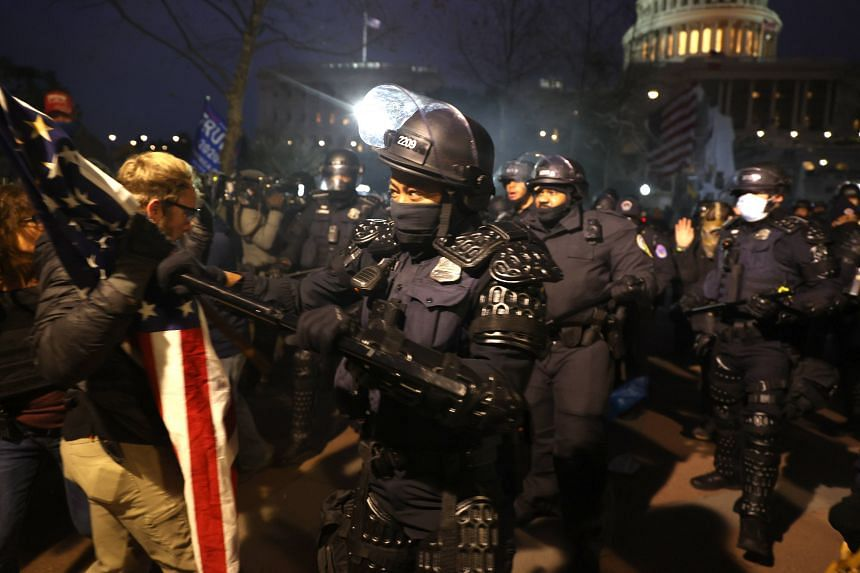 Police officers in riot gear confronting protesters in Washington on Jan 6, 2021.