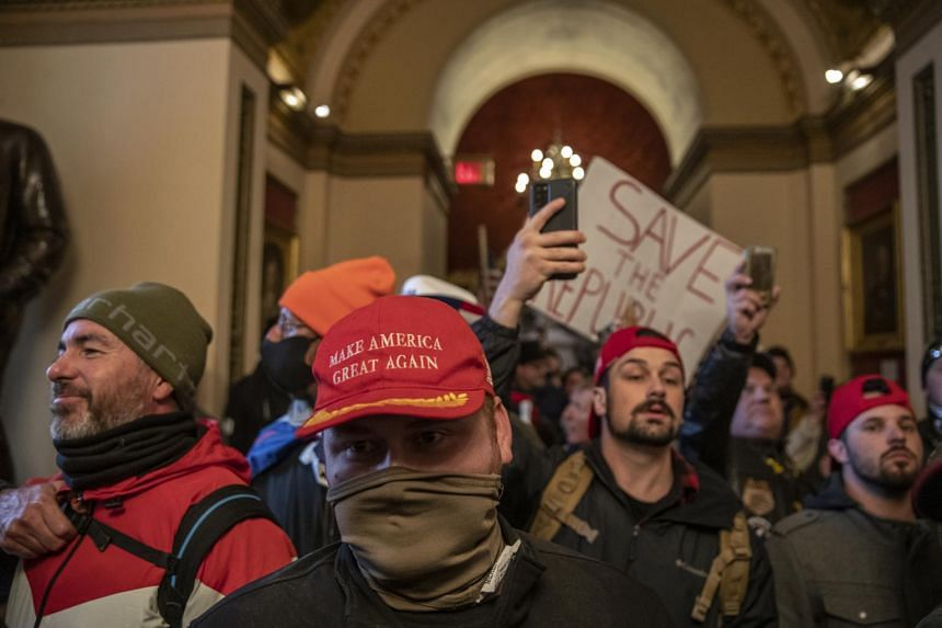 Demonstrators walk through the US Capitol in Washington after breaching barricades to the building on Jan 6, 2021.