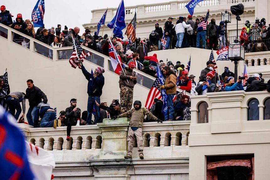 Protestors climb the US Capitol in Washington on Jan 6, 2021.