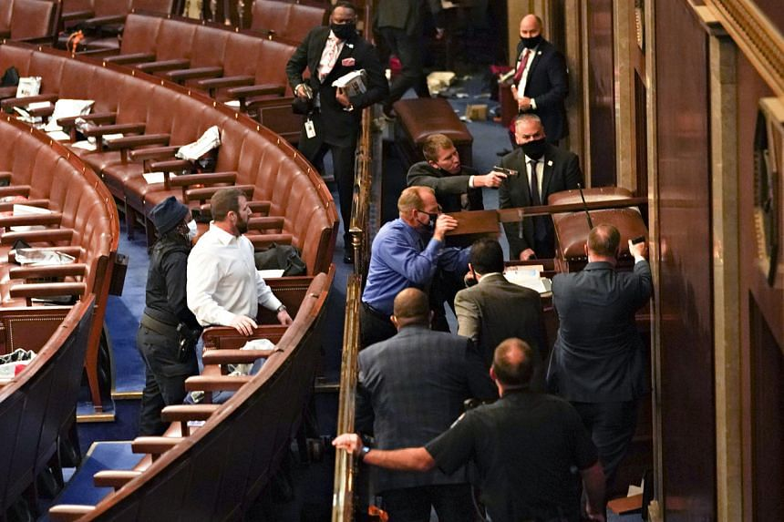US Capitol police officers point guns at a door after a joint session of Congress was suspended when pro-Trump protesters stormed barricades and breached the historic building on Jan 6, 2021.