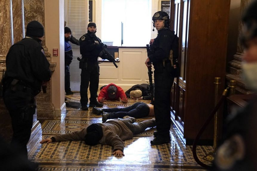 US Capitol police officers detain protesters outside of the House Chamber on Jan 6, 2021.