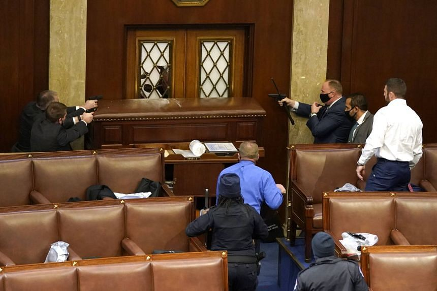 US Capitol police officers point their guns towards a door that was vandalised in the House Chamber.