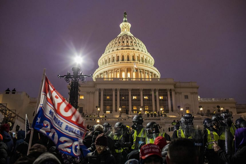 Supporters of US President Donald Trump are pushed back by police outside the Capitol in Washington on Jan 6, 2021.
