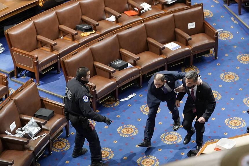 Members of the US Congress run for cover as protesters try to enter the House Chamber in the Capitol on Jan 6, 2021.