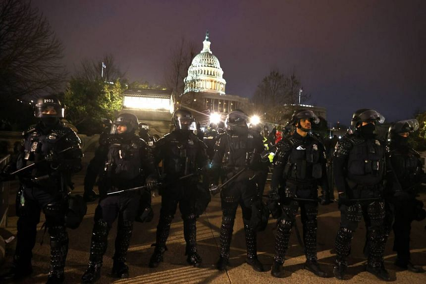 Police officers in riot gear line up at the US Capitol in Washington after protesters stormed the building on Jan 6, 2021.