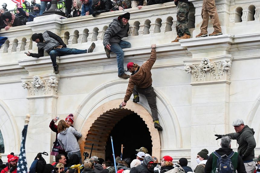 Supporters of US President Donald Trump climbing the walls of the US Capitol during a protest in Washington on Jan 6, 2021.