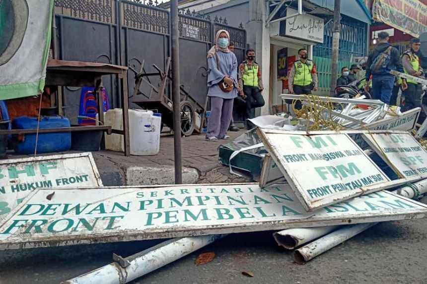 Police take down signage at the headquarters of Indonesian hardline organisation FPI in Jakarta on Dec 30, 2020.