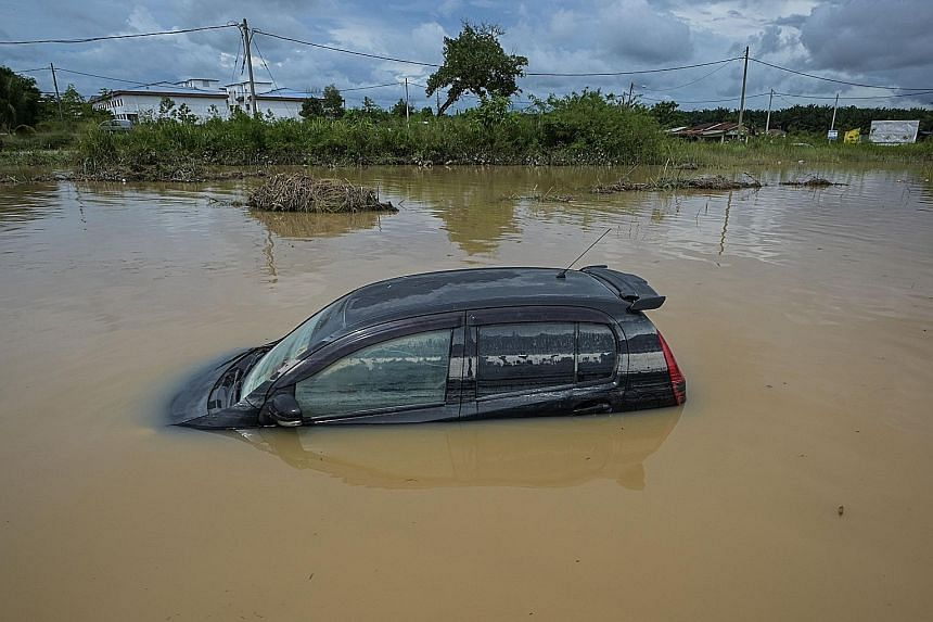 A car stranded in floodwaters after heavy rain in Temerloh, Pahang, yesterday. Malaysia's annual north-east monsoon, which runs from November to March, has caused severe flooding in several states. Pahang has been the worst affected so far, with more
