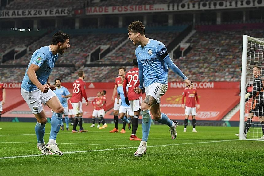 Left: John Stones (No. 5) celebrating with Ruben Dias after opening the scoring for City in their League Cup semi-final against Manchester United at Old Trafford. Below: Fernandinho sealing the 2-0 win for City, who will go for a fourth straight Leag