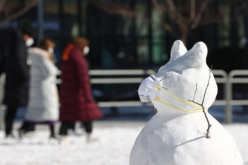 A masked snowman standing in front of an outdoor Covid-19 testing station in Seoul yesterday, as heavy snowfall hit South Korea. Some experts attributed the cold weather to a lower carbon footprint last year, with factories shutting down during the c