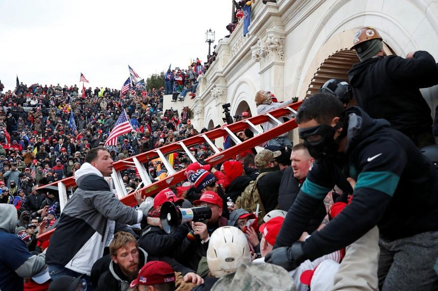 Protesters breach the barricades of the US Capitol in Washington on Jan 6, 2021.