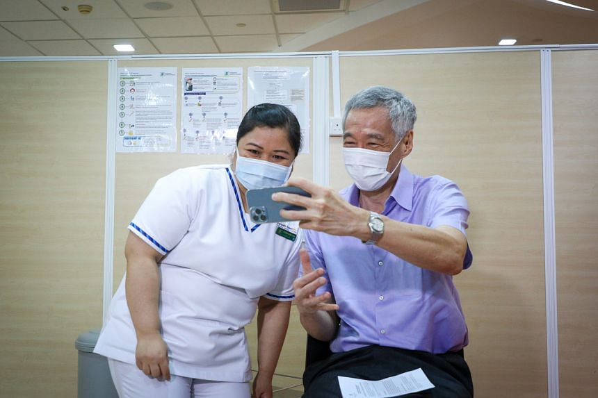 PM Lee taking a photo with SGH senior staff nurse Fatimah Mohd Shah, who administered his Covid-19 vaccine, on Jan 8, 2021.