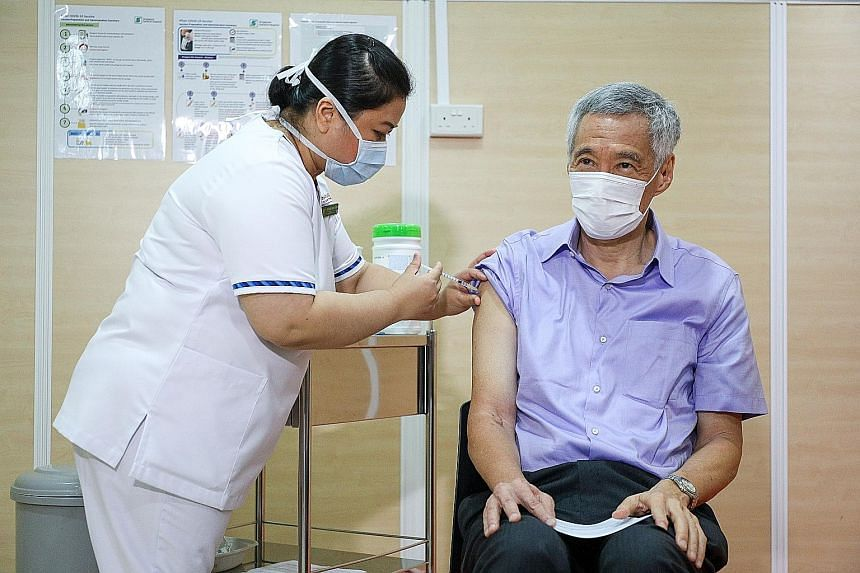Senior staff nurse Fatimah Mohd Shah, 41, administering the vaccine shot for Prime Minister Lee Hsien Loong at Singapore General Hospital yesterday. He told reporters that it was painless, effective and important. PHOTO: LIANHE ZAOBAO