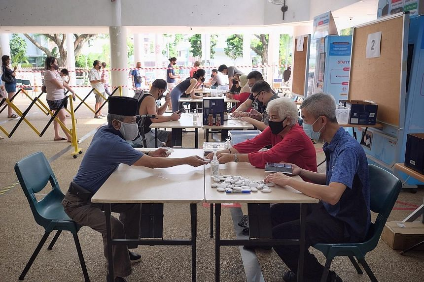 Residents collecting their TraceTogether tokens at a community centre last month. Some observers feel that limiting the use of the data would help balance the need to fight Covid-19 with the need to fight serious crime. ST PHOTO: GAVIN FOO