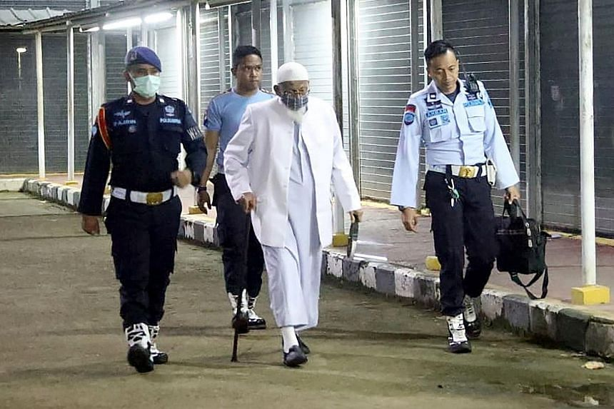 Mr Abu Bakar Bashir, 82, the spiritual leader of South-east Asia's terrorist group Jemaah Islamiah, being escorted out by prison guards yesterday as he left the Gunung Sindur prison in Bogor, on the outskirts of Jakarta. The radical cleric had been i