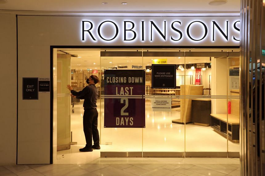 A Robinsons employee closing the doors of the Raffles City outlet after the last customer left at 3.57pm on Jan 9, 2021.